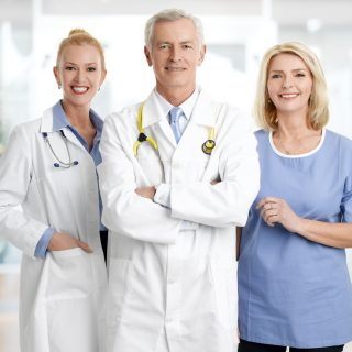 Medical staff portrait. Female doctor and male doctor standing with nursing assistant at hospital while smiling and looking at camera.